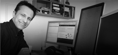 [Photo: Z-omo founder Colin Tester, working at his desk—no fewer than three monitors are required.]